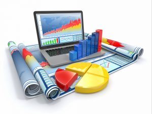 image - business analytics - laptop with physical props of graphs, pie charts, bar charts